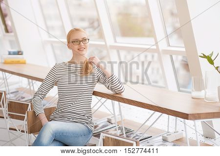 We always need fresh ideas. Shot of beautiful young businesswoman sitting at her desk and looking out window