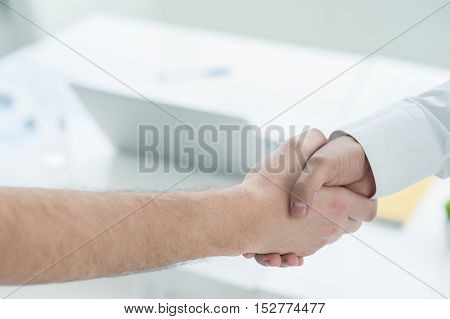 Sealing the deal. Top view of business people shaking hands over deal