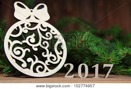 new year 2017,Christmas-tree decoration with a branch of a fir-tree and wooden figures of the coming year, New Year's composition