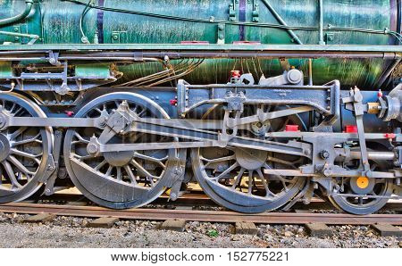 Wheels of a green steam locomotive. HDR image