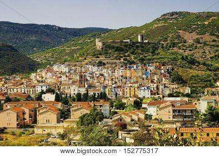 Beautiful landscape in Bosa with green hills colorful houses of the district Sa Costa and and the Castle - il Castello di Serravalle also called il Castellos di Malaspina in Sardinia Italy.