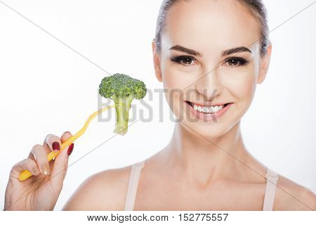 Happy fit girl is holding broccoli on fork and smiling. She is standing and looking at camera with confidence. Isolated