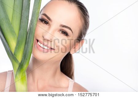 I like healthy food. Beautiful young woman is touching leek to her face. She is smiling and looking at camera with pleasure. Isolated and copy space in right side