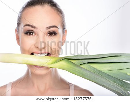 Slim young woman is standing and eating leek. She is holding it in mouth and looking forward with desire. Isolated