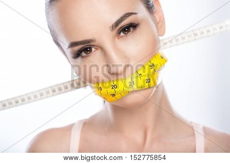 Eating is forbidden. Serious young woman is dieting. She is standing and shutting mouth by tape-measure. Isolated