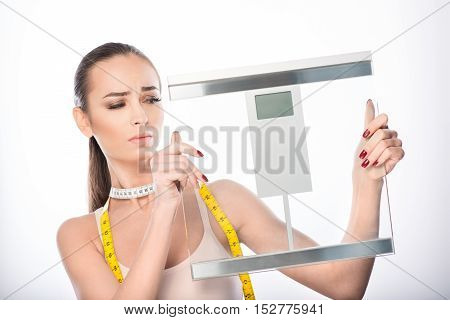 Sad young woman is holding scales and looking at it with frustration. She is standing and carrying tape-measure. Isolated