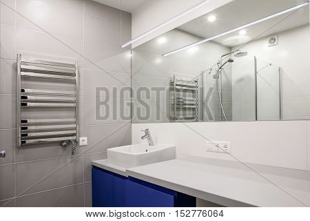 interior of a modern bathroom with a mirror sink and heater