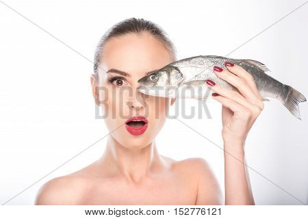Healthy young girl is holding fish and covering eye with it. She is standing and looking at camera with shock. Isolated