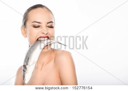 Wild naked woman is holding fish in mouth with hunger. Isolated and copy space in right side
