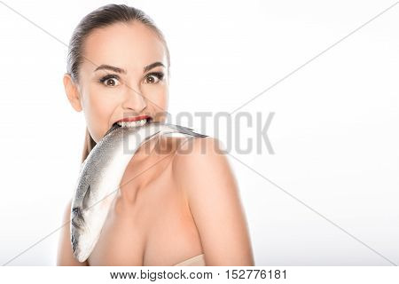 I am very hungry. Young girl is eating seafood. She is standing and looking at camera with passion. Isolated and copy space in right side