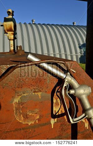 A gas and diesel nozzle is hooked unto a fuel tank.