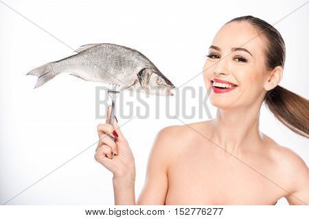 Happy girl is ready to eat fish. She is holding for and smiling. Isolated