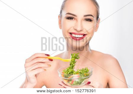 Happy young woman is eating salad and smiling. She is standing and holding bowl. Isolated