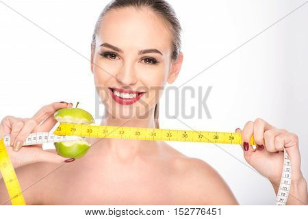 Eat apple and be slim. Happy young woman is measuring bitten apple by tape. She is standing and smiling. Isolated