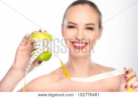 Eat vitamins and your waist will be slim. Happy young girl is showing bitten apple measured by tape. She is standing and laughing. Isolated