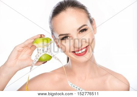 Joyful girl is dieting by eating fruits. She is holding apple wrapped by tape measure and looking at camera with satisfaction. Lady is standing and smiling. Isolated