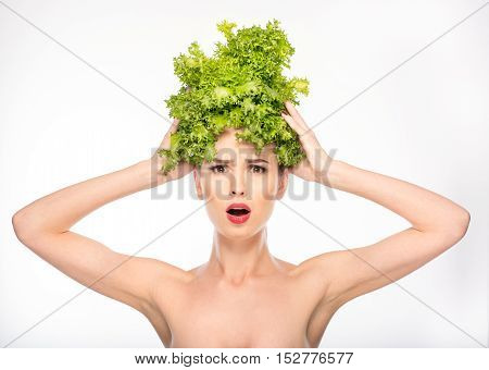 What happens with my hair. Surprised young woman is touching lettuce on her head. She is standing and looking forward with shock. Isolated