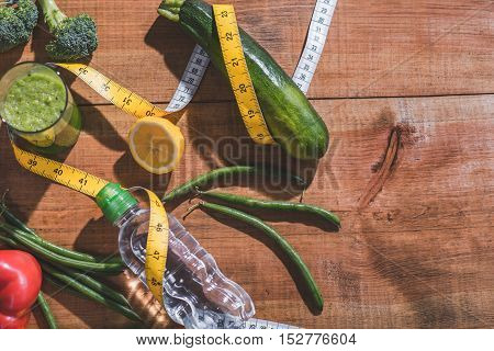 Close-up of fresh vegetables and fruits, water and juice on wooden table. Measuring tape around it