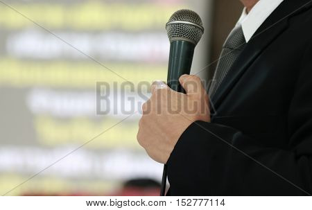 blurred of businessman presentation or speech with microphone