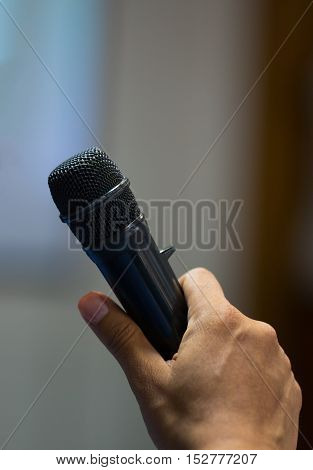 male hand holding with microphone reporter in meeting room