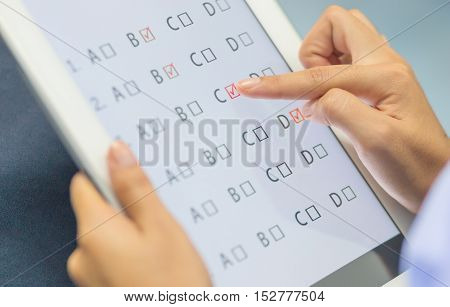 student testing in exercise exams answer on a tablet with multiple-choice questions by finger clicking