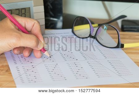 student testing exams test paper answer sheet with pencil and digital clock : education concept