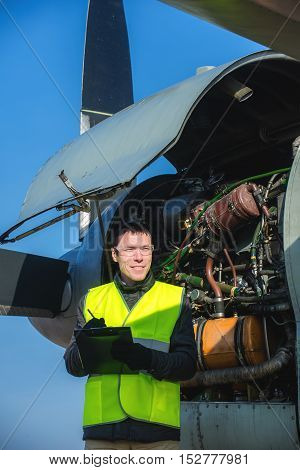 Young male engineer checking airplane's engine at airport