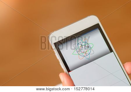 Student doing online tutorials about geometry. on mobile phone brown background
