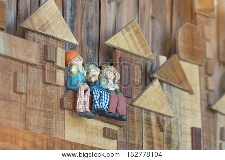 happy miniature people ceramic dolls sitting on wood wall for interiors home