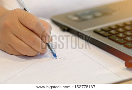 Close up of woman hand writing signature with documents and using modern laptop computer