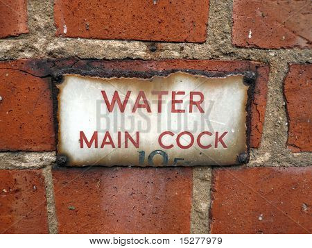 Red brick wall with aged water mains sign that has rusted