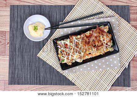 Japanese pizza (Okonomiyaki in Japanese) is fried mixed vegetable flour with meat topped sweet sauce ,mayonnaise or salad cream and sliced dried yellowfin tuna served with side dish.