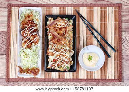 Grill flour wrap squid (as Takoyaki) served with Japan pizza (as Okonomiyaki) and side dish.