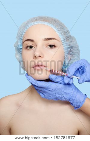 Attractive young woman gets cosmetic injection an injection in the upper lip over blue background. Doctors hands making an injection in face close-up. Beauty Treatment. shot in the lower lip