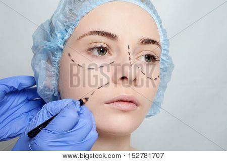 Beautiful young woman with perforation lines on her face before plastic surgery operation. Beautician touching woman face and draws a pencil or marker. concept of beauty.