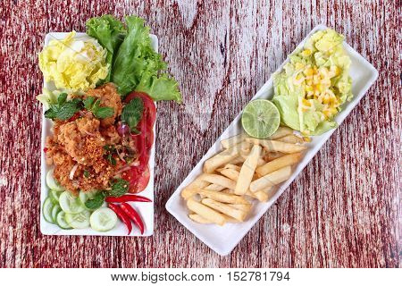 Spicy fried chicken salad (Yum Kai Zap in Thai) served mixed vegetables salad and french fires.
