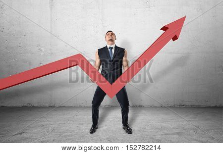 Businessman holding a big red line graph with an upturned arrow and trying to raise it up with his muscular arms. Working hard to increase incomes. Making efforts to grow profits. Improving business success rate.