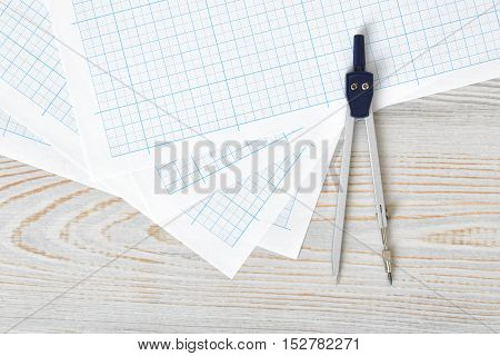 Compass on graph paper in top view with copy space. Workplace of architect, constructor, designer. Start a new project. Construction and architecture. Tools for drawing.