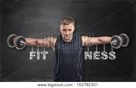 Sportsman lifts dumbbells for training his deltoids. Fitness and sport. Power training. Healthy lifestyle.
