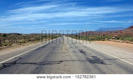 Deserted road through the vast wild plains of Utah, USA. Light, natural colors.
