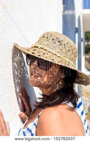 Side view of black-haired woman in sunglasses and straw hat up against the wall