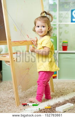 Child girl writing on whiteboard in nursery