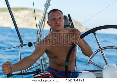 Young man skipper steers wheel the sailing yacht boat. Vacation, holidays, travel.