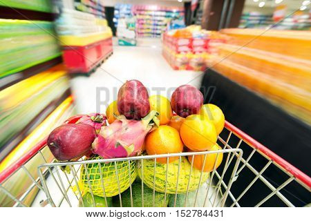 A shopping cart filled with fruit inside the supermarket.
