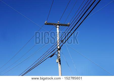 power pole under blue sky, vertical composition