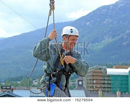 Man in helmet and harness, zip-trekking