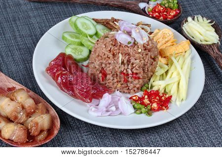 Fried jasmine rice with shrimp paste,(Kao Klok Kapi in Thai) served with green mango,Chinese sausage,crispy dried fish,shrimp,minced chili,shallots,stir sweet pork,cucumber and egg.Selective focus.