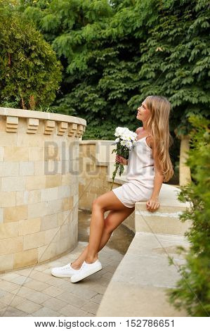 Pretty attractive girl holding a bouquet of daisies. She is wearing a white dress.