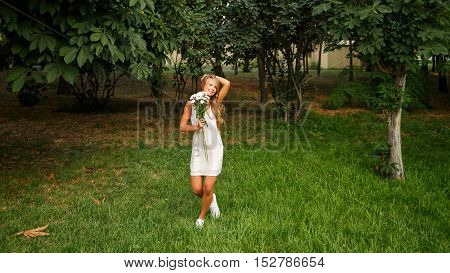 Pretty attractive girl holding a bouquet of daisies. She is in a white dress standing on a lawn and straightens her hair in the park.