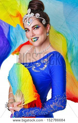 Attractive girl dancing with a rainbow fan. Stage makeup and image.